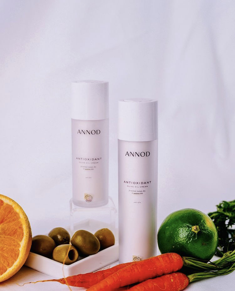 A set consisting a 30 ml and 50ml of of Annod's Anti-Oxidant Olive Oil Cream placed in the centre with natural ingredients like carrots, avocado and olives