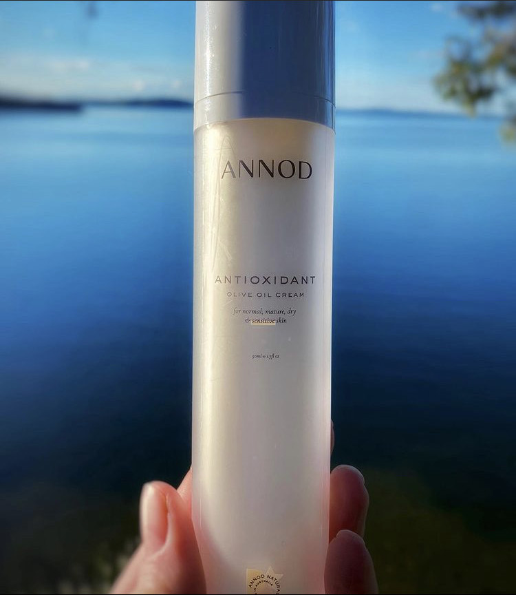 A 50ml bottle of Annod's Antioxidant Olive Oil Cream held by a customer in front of a blue lake.