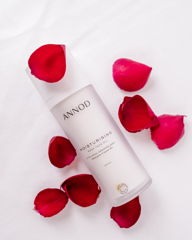 A bottle Annod's Moisturising Rose Face Oil with rose petals